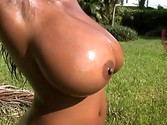 Busty black slut Maserati shaking her oiled H tits outdoor