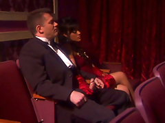 Dark haired bombshell Kaylani Lei gives a handjob to some man in a theatre
